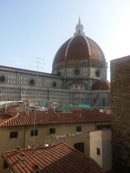 Cathedral and bell Tower as seen threw a window opening with the rooftops of Florence