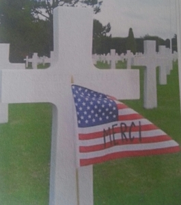 "The French word ""Merci"" or ""Thanks"" written on the American flag in front of a white cross in the Normandy American Cemetery and Memorial"